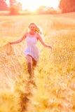 Glückliches junges blondes Mädchen im weißen Kleid mit laufendem Th des Strohhutes Stockfoto