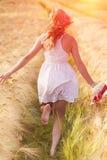 Glückliches junges blondes Mädchen im weißen Kleid mit laufendem Th des Strohhutes Lizenzfreie Stockfotografie