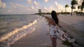 Glückliches junges brunette Frauengehen, -betrieb und auf einem tropischen Strand nahe Cancun, Mexiko bei Sonnenuntergang -spiele stock footage