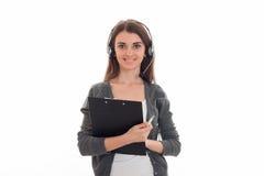 Glückliches junges Call-Center-Büromädchen mit den Kopfhörern und Mikrofon, welche die Kamera betrachten und mit Brett in ihr läc Stockfoto