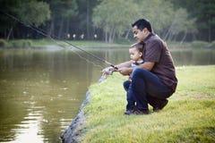 Glückliches junges ethnisches Vater-und Sohn-Fischen Stockbilder