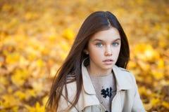 Glückliches junges kleines Mädchen im beige Mantel stockfoto