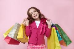 Glückliches junges langhaariges Mädchen, das im Handlos bunten Einkaufstaschen mit dem Einkaufen mit einem erfüllten Ausdruck auf Lizenzfreies Stockbild