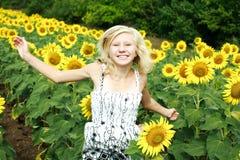 Glückliches junges Mädchen, das auf dem Gebiet springt Stockbild