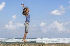 Glückliches junges Mädchen, das auf den Strand springt stockfoto
