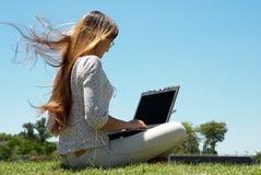 Glückliches junges Mädchen, das an einem Laptop lächelt und arbeitet Lizenzfreie Stockfotografie