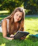 Glückliches junges Mädchen, das einen Tablettecomputer verwendet Stockfotos