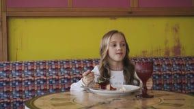 Glückliches junges Mädchen, das geschmackvollen Nachtisch isst und Fenster betrachtet 4K stock video