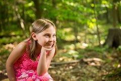 Glückliches junges Mädchen, das im Holz betrachtet Kopien-Raum sitzt Lizenzfreies Stockbild