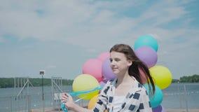 Glückliches junges Mädchen, das mit bunten Ballonen auf der Sommerbucht aufwirft stock footage