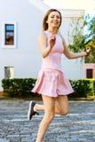 Glückliches junges Mädchen, das oben in ein rosa Kleid mit einem Blumenstrauß springt stockbilder