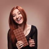 Glückliches junges Mädchen des Porträts mit der großen Schokolade Stockfotos