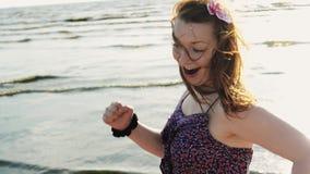 Glückliches junges Mädchen mit Blume im Haar laufen fastly auf Strandlächeln in camera sonnig stock video footage