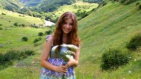 Glückliches junges Mädchen mit einem Blumenstrauß von Gänseblümchen in einer Wiese stock video footage