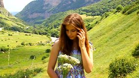 Glückliches junges Mädchen mit einem Blumenstrauß von Gänseblümchen in einer Wiese stock footage