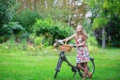 Glückliches junges Mädchen mit Fahrrad und Blumen Stockbild