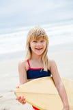 Glückliches junges Mädchen mit Surfbrett auf Strand Stockfotografie