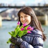 Glückliches junges Mädchen in Paris mit Tulpen Stockfoto