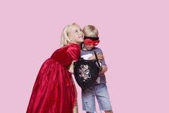 Glückliches junges Mädchen in Prinzessinkostüm, das den Jungen vortäuscht, ihr Held über rosa Hintergrund zu sein umarmt Lizenzfreie Stockfotografie