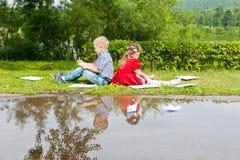Glückliches junges Mädchen und Junge Schreiben Herein lächeln Stockfotos