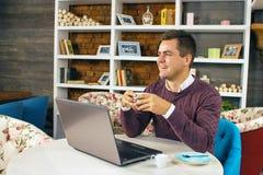 Glückliches junges Mannlächeln und -arbeiten über seinen Laptop Lizenzfreies Stockfoto
