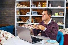 Glückliches junges Mannlächeln und -arbeiten über seinen Laptop Stockfoto