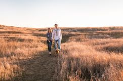 Glückliches junges Paar geht mit Hund lizenzfreie stockfotografie
