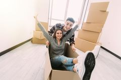 Glückliches junges Paar hat Spaß mit Pappschachteln im neuen Haus an beweglichem Tag lizenzfreies stockbild