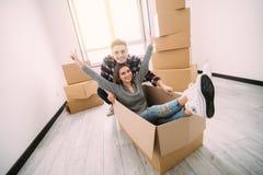 Glückliches junges Paar hat Spaß mit Pappschachteln im neuen Haus an beweglichem Tag stockfoto