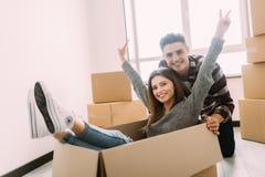 Glückliches junges Paar hat Spaß mit Pappschachteln im neuen Haus an beweglichem Tag stockbilder