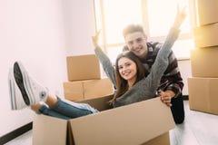 Glückliches junges Paar hat Spaß mit Pappschachteln im neuen Haus an beweglichem Tag stockbild