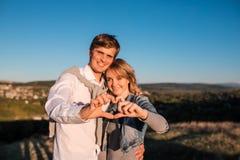 Glückliches junges Paare ` s, das Herz von den Fingern macht stockbild