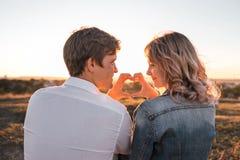 Glückliches junges Paare ` s, das Herz von den Fingern macht stockfoto