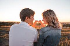 Glückliches junges Paare ` s, das Herz von den Fingern macht lizenzfreie stockfotos