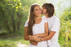 Glückliches junges Paarküssen im Freien Stockfoto