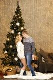 Glückliches junges Paartanzen durch den Weihnachtsbaum Stockbilder