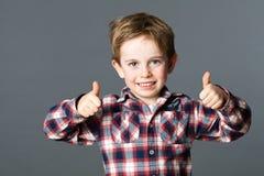 Glückliches junges rotes Haarvorschulkind mit den Daumen oben Stockbilder