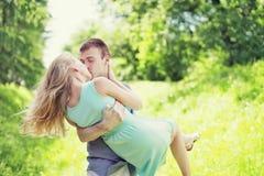 Glückliches junges süßes Paar küsst, Mann und verliebte Frau, hält er sie auf Hände am Gras lizenzfreie stockfotos
