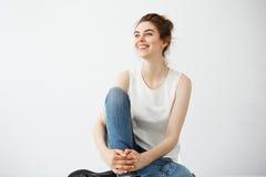 Glückliches junges schönes Brunettemädchen mit dem lächelnden lachenden Sitzen des Brötchens über weißem Hintergrund Stockbild