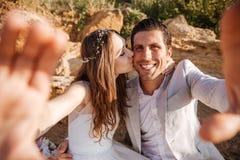 Glückliches junges verheiratetes Paar, das selfie am Strand macht Lizenzfreie Stockfotografie