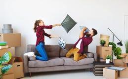 Glückliches junges verheiratetes Paar zieht auf neue Wohnung und dem Lachen, Sprung, Kampfkissen um stockbilder