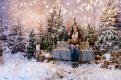Glückliches junges weibliches Sitzen auf einer Bank oder ein Schwingen über dem Blitz Lizenzfreie Stockfotografie