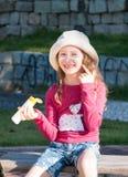 Glückliches kaukasisches Mädchen, das Sonnenblock auf seinem Gesicht verwendet Stockbild