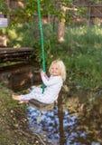 Glückliches Kind auf Baumschwingen Stockbilder