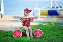 Glückliches Kind auf dem Seetropischen Strand mit Wassermelone in den Händen genießen das Lebenszeitwochenende fantastische stilv stockfotografie