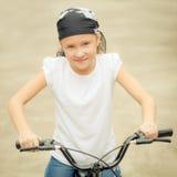 Glückliches Kind auf einem Fahrrad Stockfotos