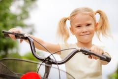 Glückliches Kind auf einem Fahrrad Stockbilder