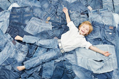 Glückliches Kind auf Jeanshintergrund. Denimart und weise Stockfoto