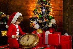 Glückliches Kind betrachtet die große Uhr in Sankt-Hut Kind wartet auf das neue Jahr Weihnachtsniederlassung und -glocken feierta lizenzfreie stockfotografie