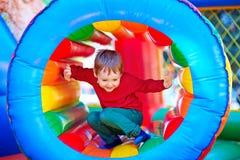 Glückliches Kind, das auf aufblasbarem Anziehungskraftspielplatz spielt Lizenzfreie Stockbilder